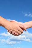 Hand shake between a man and a woman. On blue sky background Stock Photo