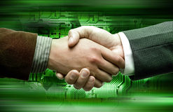Hand shake over electronic device background. Hand shake of two leaders over electronic device background Royalty Free Stock Photography