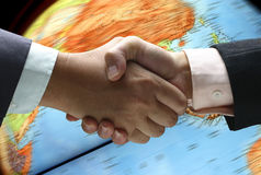 Hand shake over globe Royalty Free Stock Photos