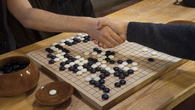 Hand shake before play Chinese board game Go or Weiqi. For respect Royalty Free Stock Image