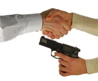 Hand shake under a barrel of a pistol Royalty Free Stock Images