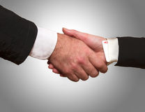 Hand shake between a woman and a man. Woman hand with ace up the sleeve hand shake with man Royalty Free Stock Image