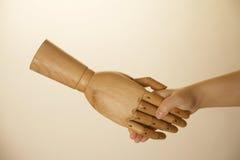 Hand shaking wooden hand Stock Image