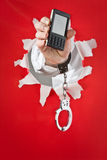 Hand in shakles hold mobile telephone Stock Images