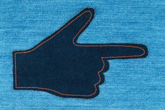 Hand in the shape a pointer made of denim jeans lies on a jeans Royalty Free Stock Image