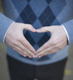 Hand shaped heart. Close up of single man's hands making a heart shape as he is wearing a blue sweater Stock Photography