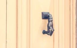 Hand shaped Metal Knocker on Beige Wooden door. Malta Stock Photos