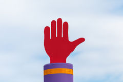 Hand shaped road sign. Red hand shaped road sign against the sky Stock Image