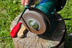Hand sharpening knives with electric grinder tool Stock Images