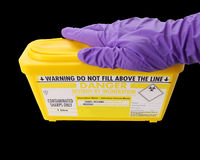 Hand on sharps box Royalty Free Stock Photo