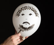 Hand shaves a white ballon on a black background Royalty Free Stock Image