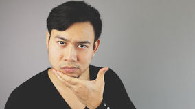 Hand shaving his chin. An asian man with black t-shirt royalty free stock image