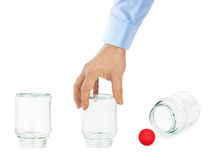 Hand and shell game with glass cans Stock Photos