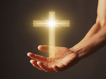Hand with a shining cross Royalty Free Stock Images