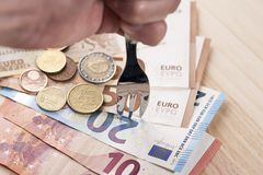 A hand with a shiny metallic fork beats a pile of banknotes and euro coins. On a wooden table. Concept of saving cash and tax evasion stock images