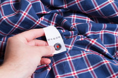 Hand shirt and label with instructions Stock Photography