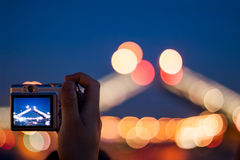 Hand shooting night photo of bridge. Hand with a silver compact camera shooting night scene, selective focus on a camera with lens blur on background Stock Photography