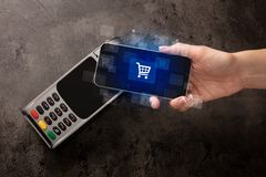 Hand shopping with mobile phone. Easy paying with mobile phone in the marketn royalty free stock photo