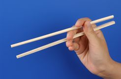 Hand with shopstick. One hand is holding some shopsticks royalty free stock image