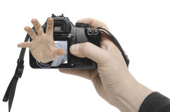 Hand Shot. A hand appears out of the display of a digital camera Stock Image