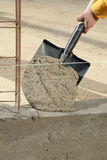 Hand and shovel. Hand applying cement with a shovel on a wall in progress Royalty Free Stock Photography