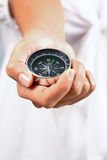 Hand show a compass. On the plain background Stock Images