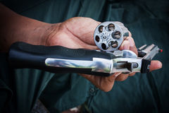 Hand show gun emptied storage cylinder of revolver h Royalty Free Stock Photo