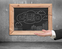 Hand showing blackboard with hand-drawn app icons on wall Stock Photos