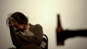 Hand showing bottle with beer alcohol addicted woman, rehabilitation, willpower stock photography