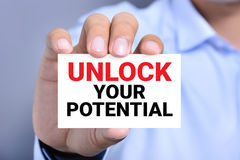 Hand showing card with message UNLOCK YOUR POTENTIAL Stock Image