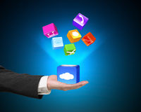 Hand showing cloud box illuminated app icons  on blue Stock Photo