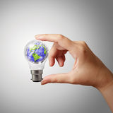 Hand showing crumpled world paper symbol in light bulb. As concept Stock Photo