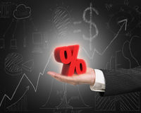 Hand showing 3D red percentage sign with business doodles blackb. Hand showing 3D red percentage sign with business concept doodles blackboard background Royalty Free Stock Image