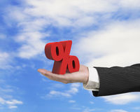 Hand showing 3D red percentage sign with sky cloud Stock Images