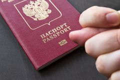 Hand showing the fig sign, on red russain passport background.  stock images
