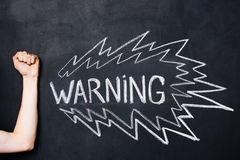 Hand showing fist near warning drawn on blackboard Stock Images