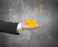 Hand showing gold jigsaw puzzle piece with business concept dood. Les wall background Stock Images