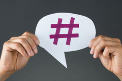 Hand Showing Hashtag On Speech Bubble. Closeup of hand showing hashtag on speech bubble against gray background Royalty Free Stock Photography