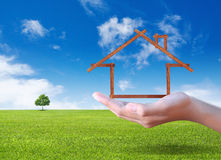Hand showing House on the green field Royalty Free Stock Photography