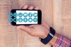 Hand showing mobile phone with icons Stock Images