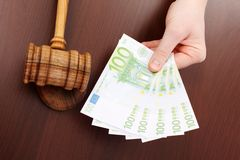 Hand showing money near justice gavel Stock Photography