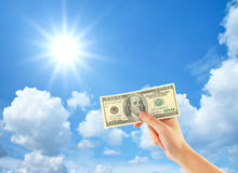 Hand showing money over sky Stock Image