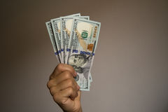 Hand showing notes of one hundred dollars. Stock Photos