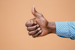 Hand showing OK sign isolated on brown background. Close-up of positive gesture, like, agreement, accept concept concept Stock Photos