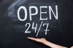 Hand showing open all the time sign drawn on blackboard Royalty Free Stock Photo