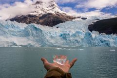 Hand showing a piece of ice from rthe spegazzini glacier in Argentina royalty free stock photo