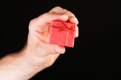 Hand showing red present box Stock Photos