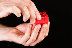 Hand showing red present box Stock Photography