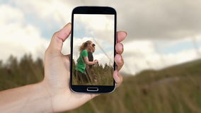 Hand showing running and adventure clips on smartphone stock footage