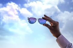 Hand showing sky through sunglass Royalty Free Stock Photo
